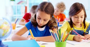 Close up of Two little Girls drawing with colorful pencils in classroom